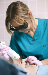 Doctor doing a laser treatment on a womans foot