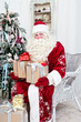 Saint Nicolas with gifts sits near Christmas fir-tree