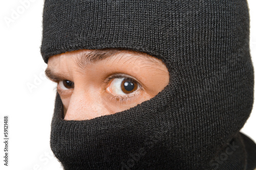 Caucasian man in black mask looks to camera