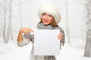 Young woman in fur hat with empty card at forest