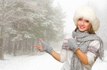 Young woman in fur hat shows pointing gesture at forest