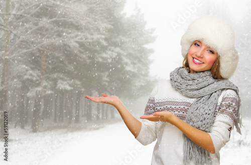 Young woman in fur hat shows welcome gesture at forest