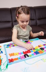 Little girl learning the alphabet using plastic letters