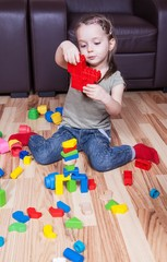 Preschool girl who build towers with cubes