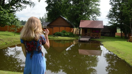 woman in dress taste glass of red wine near pond in garden