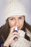 Young woman using throat spray.