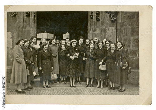 CIRCA 1949 - young women before old building