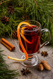 cup of mulled wine and cinnamon on wood background