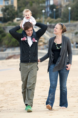 Young Couple walking on beach sand with baby