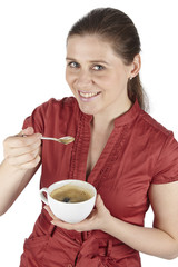 Elegante junge Frau mit Kleid trinkt eine Tasse Kaffee