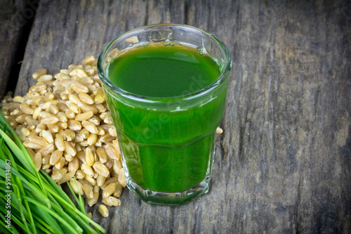 Wheat grass juice on wood background