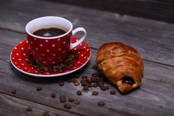 Coffee and croissant on wooden background