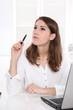 Frau nachdenklich und skeptisch sitzend im Büro