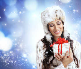 A beautiful woman holding a Christmas present on blue