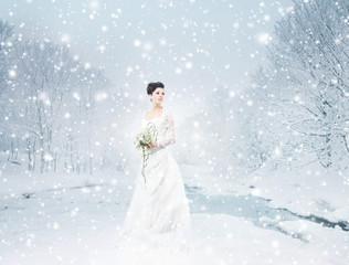A beautiful bride standing with a flower bouquet on the snow