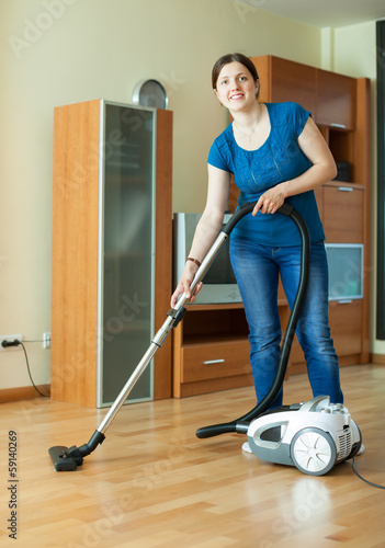 Woman  with vacuum cleaner on parquet