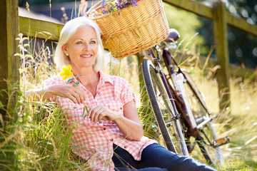 Middle Aged Woman Relaxing On Country Cycle Ride