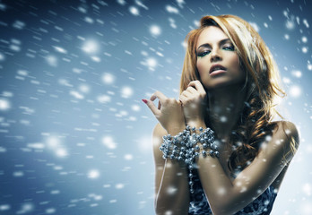 Beautiful and sexy redhead woman on a snowy background