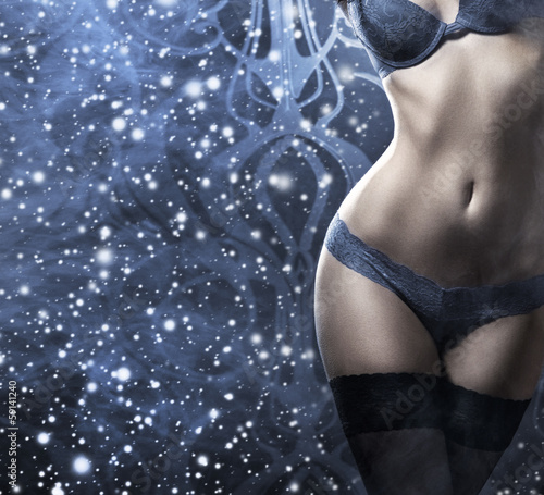 Fashion shoot of a young and sexy woman in lingerie on the snow
