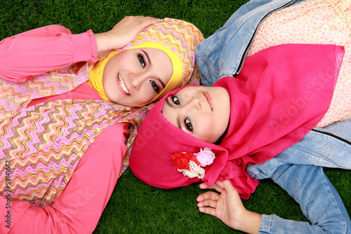 Close up of two beautiful happy muslim woman lying on grass