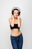 A pretty teenage girl listening to the music in headphones
