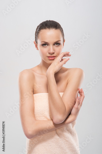 A young and attractive woman in a soft towel after taking a bath