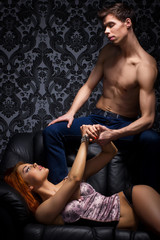 A young couple in bdsm action on a black leather sofa