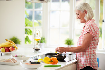 Middle Aged Woman Cooking Meal In Kitchen