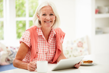 Middle Aged Woman Using Digital Tablet Over Breakfast