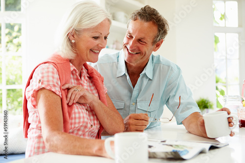 Middle Aged Woman Couple Magazine Over Breakfast