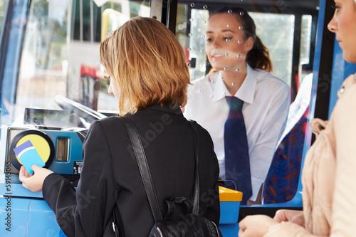 Leinwanddruck Bild Woman Boarding Bus And Using Pass