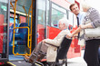Driver Helping Senior Couple Board Bus Via Wheelchair Ramp - 59145268