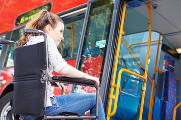 Disabled Woman In Wheelchair Boarding Bus