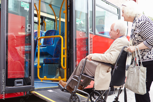 Senior Couple Boarding Bus Using Wheelchair Access Ramp - 59145235