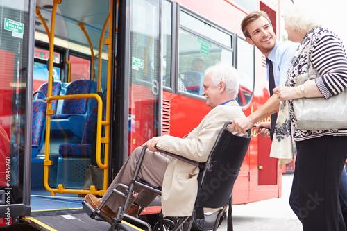 Leinwandbild Motiv Driver Helping Senior Couple Board Bus Via Wheelchair Ramp