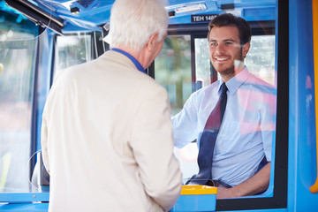 Senior Man Boarding Bus And Buying Ticket