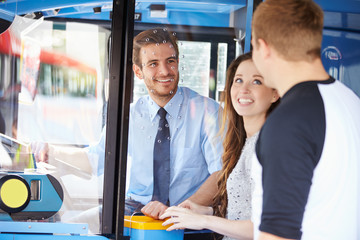 Young Couple Boarding Bus And Buying Ticket