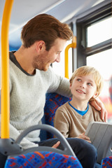 Son Using Digital Tablet On Bus Journey With Father