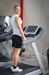 Blond young man standing on treadmill