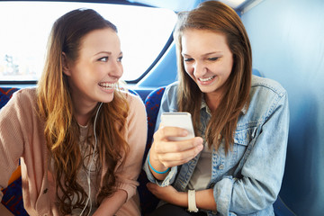 Two Young Women Reading Text Message On Bus