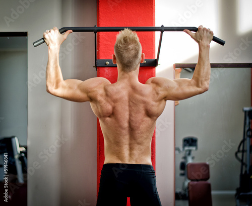 Athletic young man hanging from gym equipment