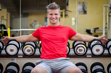 Handsome smiling young man in gym sitting on dumbbells rack
