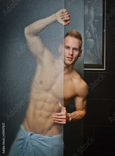 Handsome young man shirtless behind shower glass