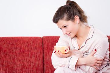 Nachdenkliche junge Frau im Pyjama