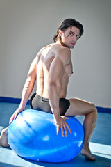 Muscular man sitting on blue fitness ball