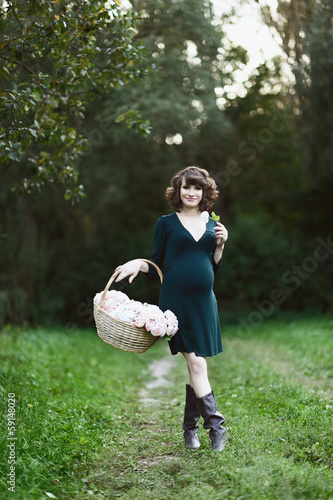 Happy young pregnant woman in the park