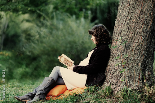 Happy young pregnant woman reading a book