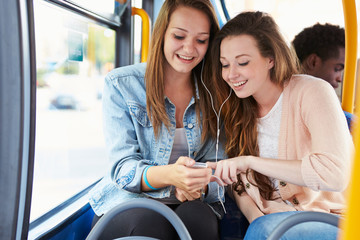 Two Young Women Listening To Music On Bus
