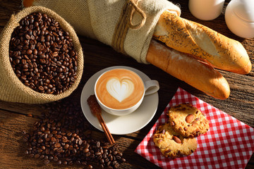 A cup of cafe latte with coffee beans and bread.