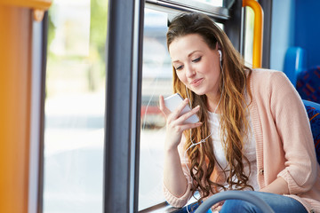Young Woman Wearing Earphones Listening To Music On Bus